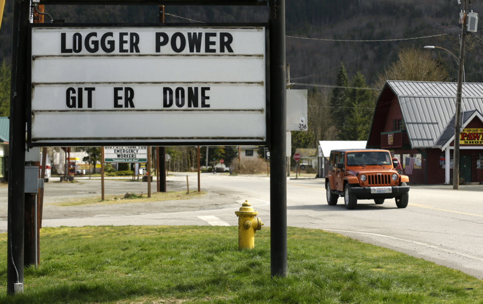 Photo - A Jeep drives past a sign that notes the Darrington High School Loggers and the encouraging phrase