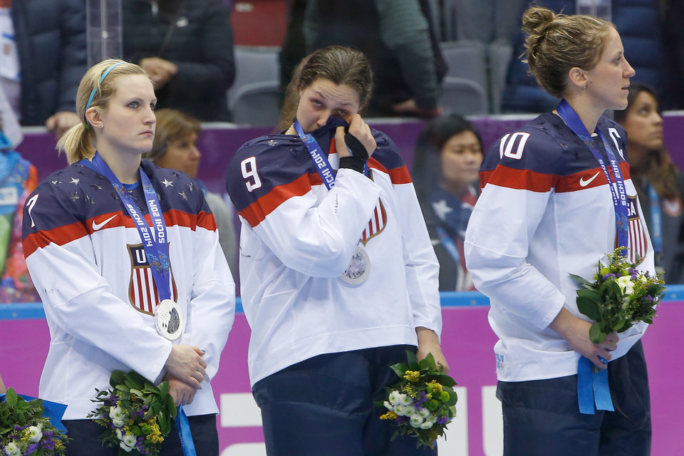 Photo - Megan Bozek of the United States (9) wipes a tear as she stand with Monique Lamoureux of the United States (7),  and Meghan Duggan of the United States (10) during the medal ceremony for the women's ice hockey tournament at the 2014 Winter Olympics, Friday, Feb. 21, 2014, in Sochi, Russia. Team USA took silver after losing 3-2 to Team Canada in overtime. (AP Photo/Matt Slocum)