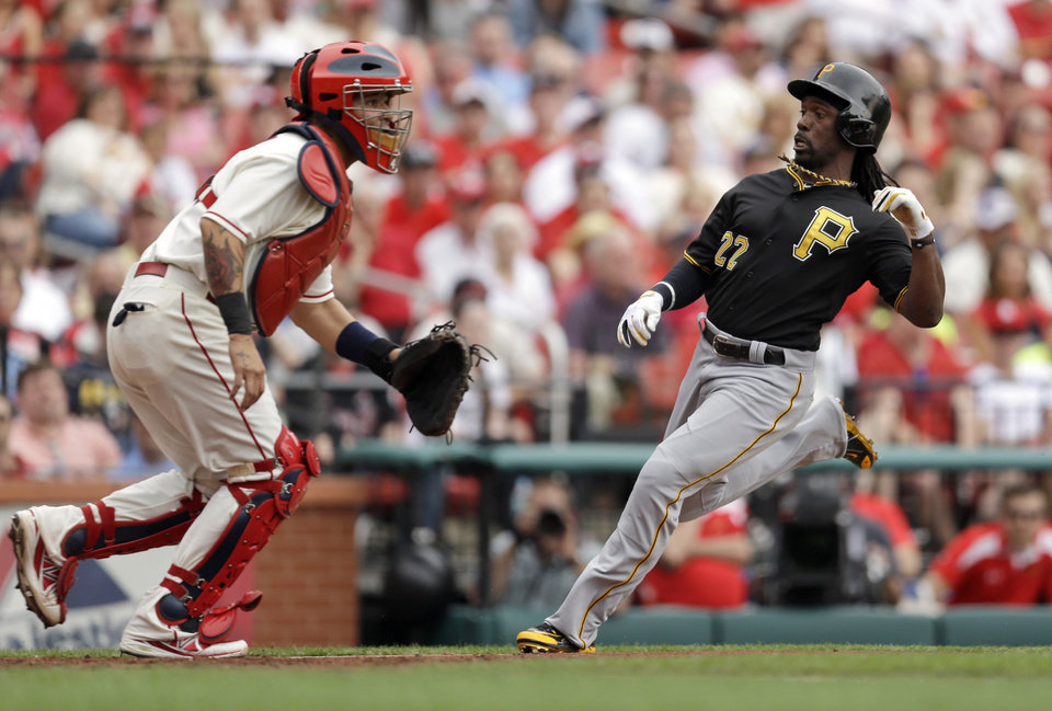 Photo - Pittsburgh Pirates' Andrew McCutchen scores on a two-run double by Gaby Sanchez as St. Louis Cardinals catcher Yadier Molina, left, looks for the throw home during the fourth inning of a baseball game Saturday, April 26, 2014, in St. Louis. (AP Photo/Jeff Roberson)