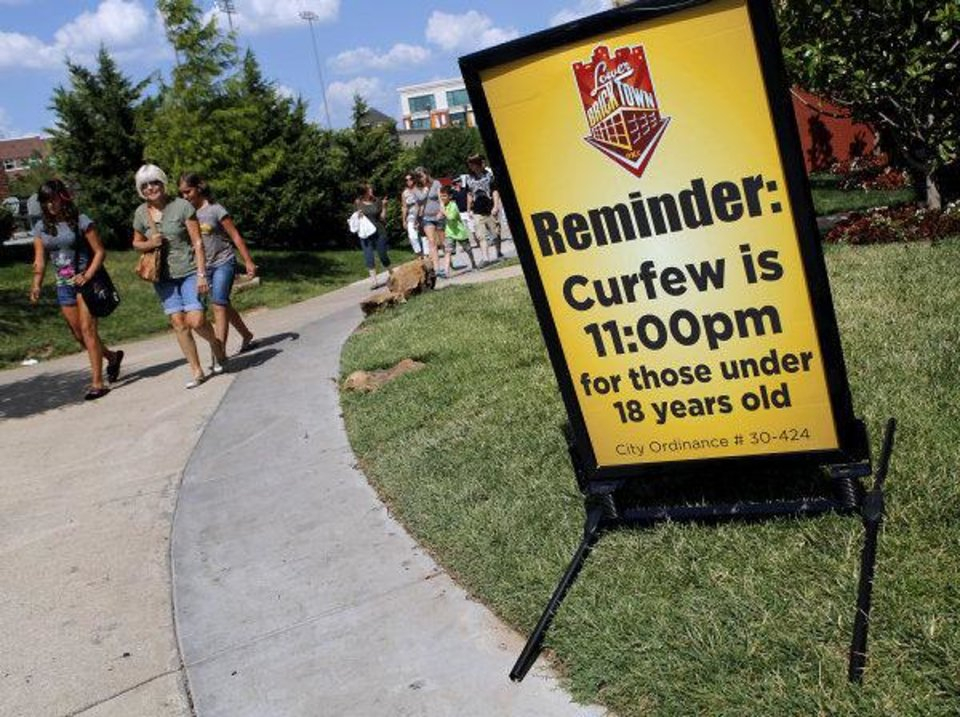Photo - A sign on the west side of Harkins Bricktown Theater in Oklahoma City reminds visitors to Bricktown of the city curfew in Bricktown on Tuesday, July 19, 2011. Photo by John Clanton, The Oklahoman