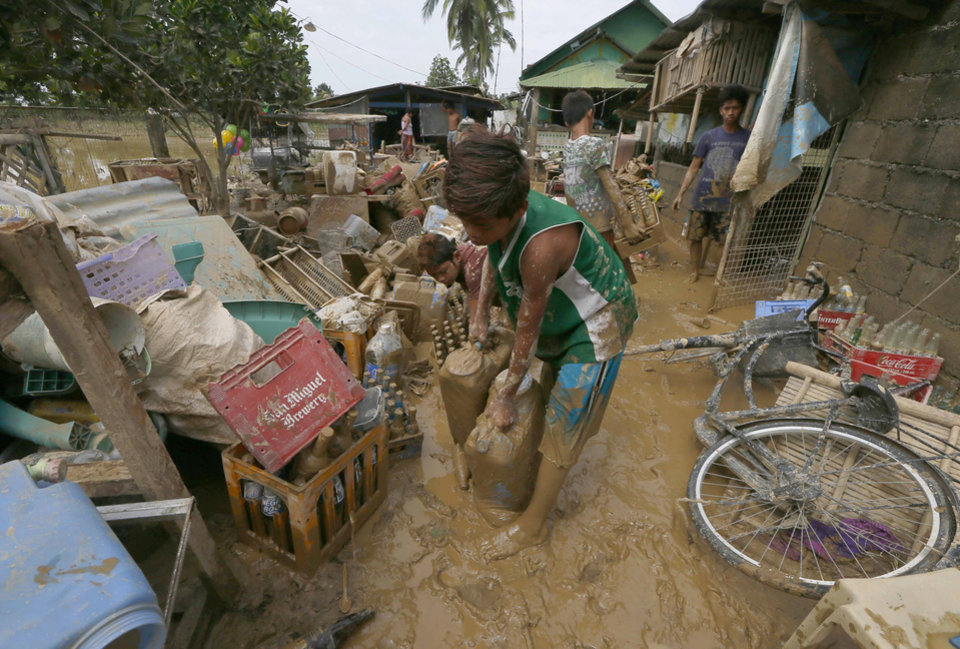 Photo - Residents begin cleaning up their homes in Cabanatuan, northern Philippines, Tuesday, Oct. 20, 2015, two days after Typhoon Koppu battered the city and nearby provinces. Slow-moving Typhoon Koppu blew ashore with fierce wind in the northeastern Philippines early Sunday, toppling trees and knocking out power and communications and forcing the evacuation of thousands of villagers. (AP Photo/Bullit Marquez)