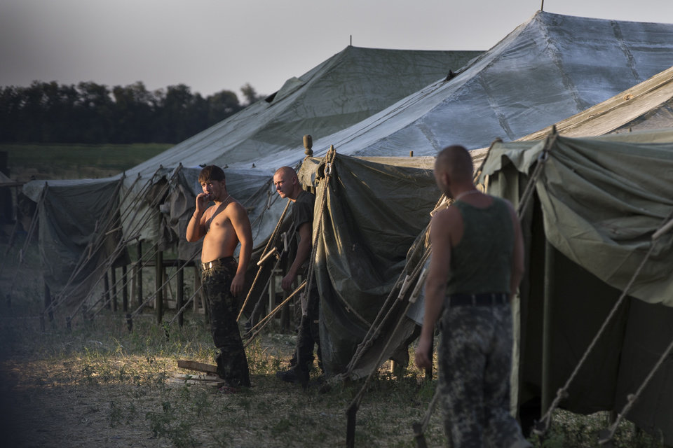Photo - Ukrainian soldiers, who fled the conflict territory, spend their time at a tent camp as the sun sets over the scene near the Russia-Ukraine border just outside the village of Gukovo, Rostov-on-Don region, Southern Russia, Monday, Aug. 4, 2014. A Russian border security official said Monday that more than 400 Ukrainian soldiers have crossed into Russia. The Russian official said the soldiers deserted the Kiev government and the Russian side opened a safe corridor. (AP Photo/Alexander Zemlianichenko)