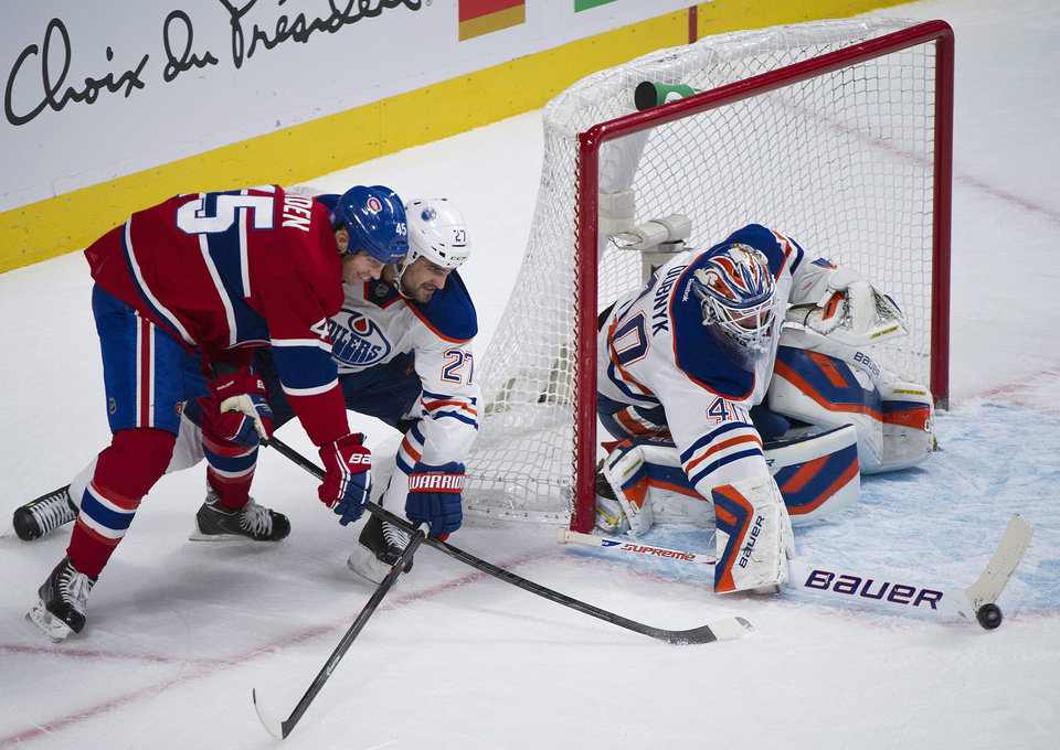 Photo - Edmonton Oilers' goaltender Devan Dubnyk, right, makes a save against Montreal Canadiens' Mike Blunden, left, as Oilers' Boyd Gordon defends during the first period of an NHL hockey game in Montreal, Tuesday, Oct. 22, 2013. (AP Photo/The Canadian Press, Graham Hughes)