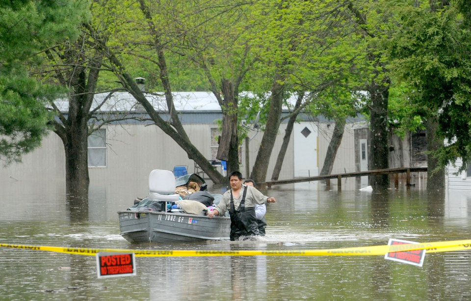 Photo - Juan Medina helps guide a boat full of personal items out of a flooded Reed Station Road Mobile Home Park on Wednesday, April 27, 2011 in Carbondale, Ill.   With five days of heavy rainfall and more to come, volunteers filling sandbags Wednesday in southern Illinois towns threatened by the swollen Ohio River braced for possible record flooding. Officials asked for more volunteers to help with the effort. (AP Photo/The Southern, Paul Newton)
