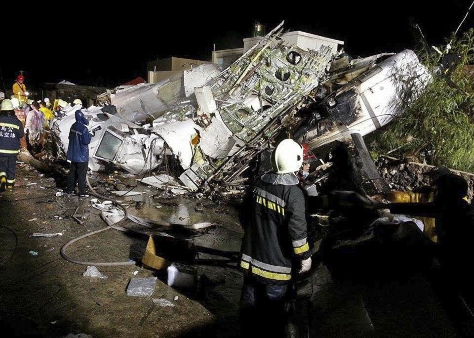 Photo - Rescue workers survey the wreckage of TransAsia Airways flight GE222 which crashed while attempting to land in stormy weather on the Taiwanese island of Penghu, late Wednesday, July 23, 2014. A transport minister said dozens of people were trapped and feared dead. (AP Photo/Wong Yao-wen)