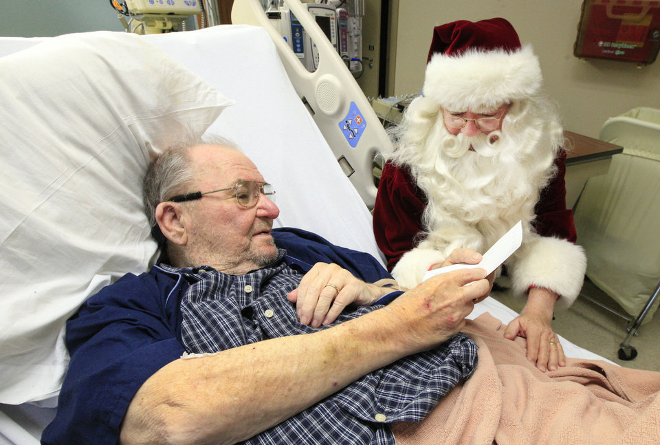 Photo - Veteran Carl Cartlidge, of Ponca City, receives a Christmas card from Santa  as cards from the Holiday Mail for Heroes program are delivered by Red Cross employees and volunteers. Photo by Paul B. Southerland, The Oklahoman  PAUL B. SOUTHERLAND - PAUL B. SOUTHERLAND