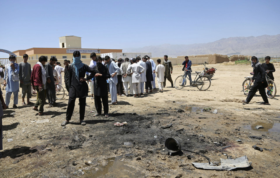 Photo - Afghans gather at the site of a suicide attack in Parwan province in eastern Afghanistan, Tuesday, July 8, 2014. An Afghan official says that at least 16 people, including four Czech soldiers, were killed Tuesday in a suicide attack near a clinic in eastern Afghanistan. A provincial spokesman says the others killed are at least 10 civilians and two police officers. The Taliban claimed responsibility for the attack in a statement sent to the media. The violence came as Afghanistan was mired in an electoral crisis after one of the candidates in the presidential elections, Abdullah Abdullah, refused to accept any results until millions of ballots are audited for fraud. (AP Photo/Rahmat Gul)