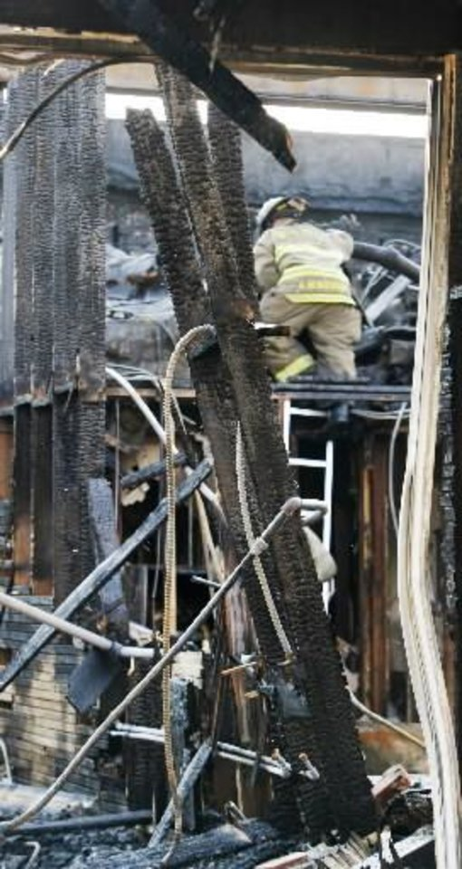 Photo - An Oklahoma City fireman climbs through the damage at Cash Express, 3630 N. Western, that burned and the roof collapsed Thursday morning, Sept. 1, 2011, in Oklahoma City. Photo by Paul B. Southerland