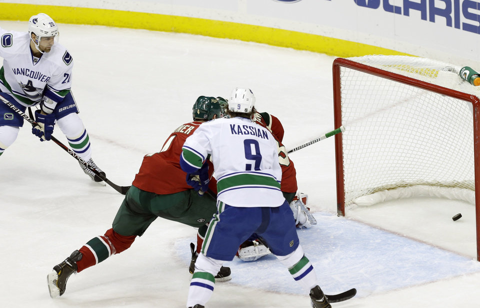 Vancouver Canucks\' Chris Higgins, left top, watches his power-play goal off Minnesota Wild goalie Niklas Backstrom, of Finland, in the first period of an NHL hockey game on Thursday, Feb. 7, 2013, in St. Paul, Minn. (AP Photo/Jim Mone)