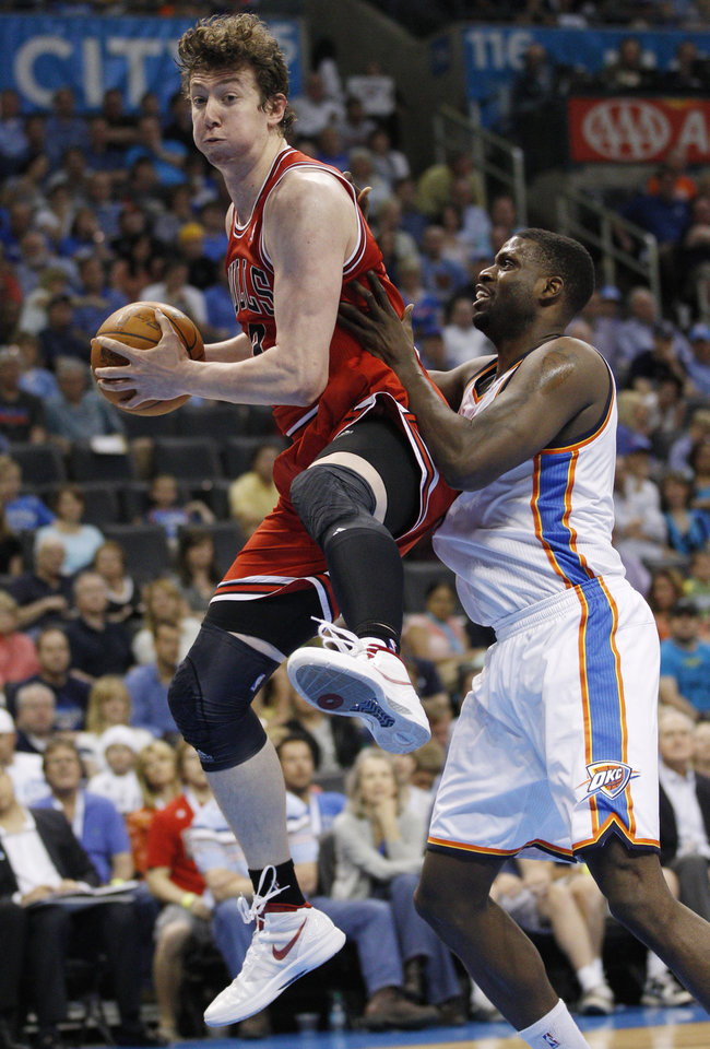 Photo -   Chicago Bulls center Omer Asik, left, grabs a rebound in front of Oklahoma City Thunder center Nazr Mohammed, right, in the second quarter of an NBA basketball game in Oklahoma City, Sunday, April 1, 2012. (AP Photo/Sue Ogrocki)