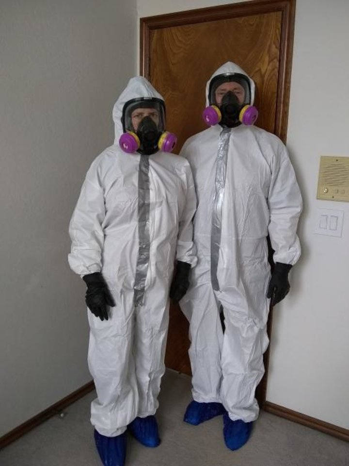Photo -  Clad in bio-hazardous suits, Michel and Marty Mayfield prep for a remediation. [PHOTO PROVIDED]
