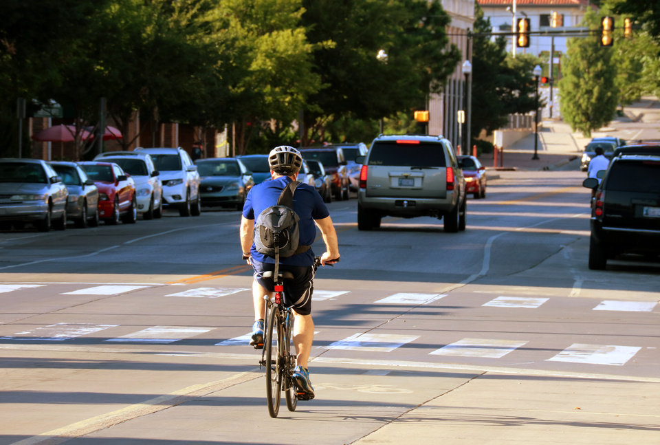 Photo -  A bicyclist makes his way north on Walker Avenue using a dedicated bike lane created as part of Project 180. [Photo by Doug Hoke, The Oklahoman Archives]
