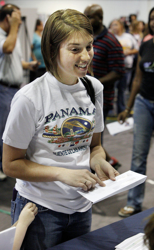Tornado victim Hayley Sanders collects a $1,000 gift card Monday at First Baptist Church in Moore. Volunteers with the Cantor Fitzgerald Relief Fund distributed more than 1,000 of the cards to families who were affected by the storm. PHOTO BY PAUL B. SOUTHERLAND, THE OKLAHOMAN <strong>PAUL B. SOUTHERLAND</strong>
