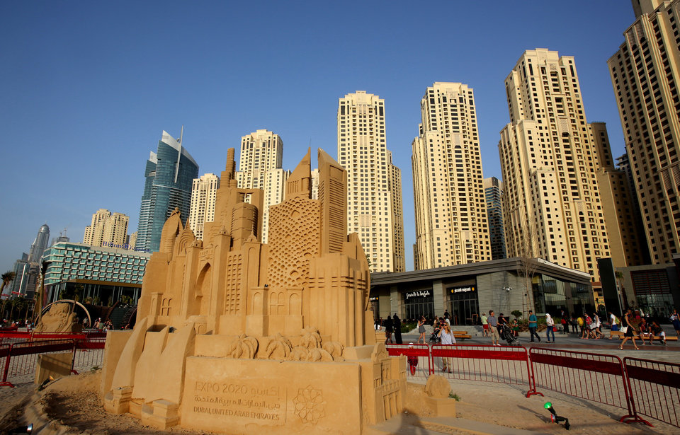 Photo - In this Monday, April 21, 2014 photo, people walk past a sand statue depicting famous landmarks of the city at the beach in Dubai, United Arab Emirates. The ribbon of beach nestled along the towering skyscrapers rising from Dubai's man-made marina district is a rare spot in the Middle East, bringing together the conservatively dressed and the bikini-clad in a multiethnic mix of those with means and those still striving for a more comfortable life. (AP Photo/Kamran Jebreili)