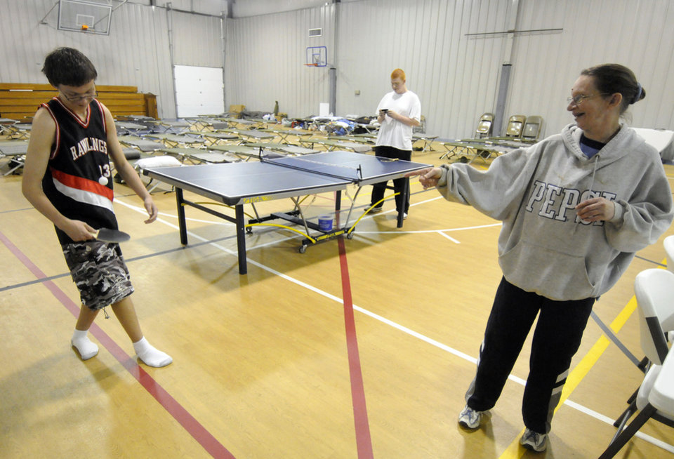 Photo - Jill Atkinson of Brookport, Ill.  jokes with her son Jimmy while he tries to bounce a ping pong ball with a paddle at the Waldo Baptist Church Wednesday, April 27, 2011. The church was serving as a Red Cross shelter for those displaced from their homes in Metropolis and Brookport due to rising floodwaters.   With five days of heavy rainfall and more to come, volunteers filling sandbags Wednesday in southern Illinois towns threatened by the swollen Ohio River braced for possible record flooding. Officials asked for more volunteers to help with the effort. (AP Photo/The Southern, Steve Jahnke)