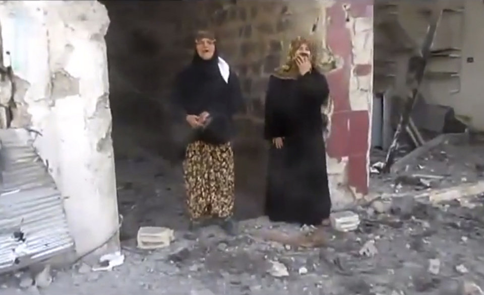 Photo -   This image taken from video obtained from Shaam News Network, which has been authenticated based on its contents and other AP reporting, shows women reacting as they stand amid rubble after heavy bombing from military warplanes, in Houla, Syria, Tuesday, Nov. 6, 2012. The Britain-based Syrian Observatory for Human Rights said air raids on Houla, a group of villages in central province of Homs, killed several people.(AP Photo/Shaam News Network via AP video)