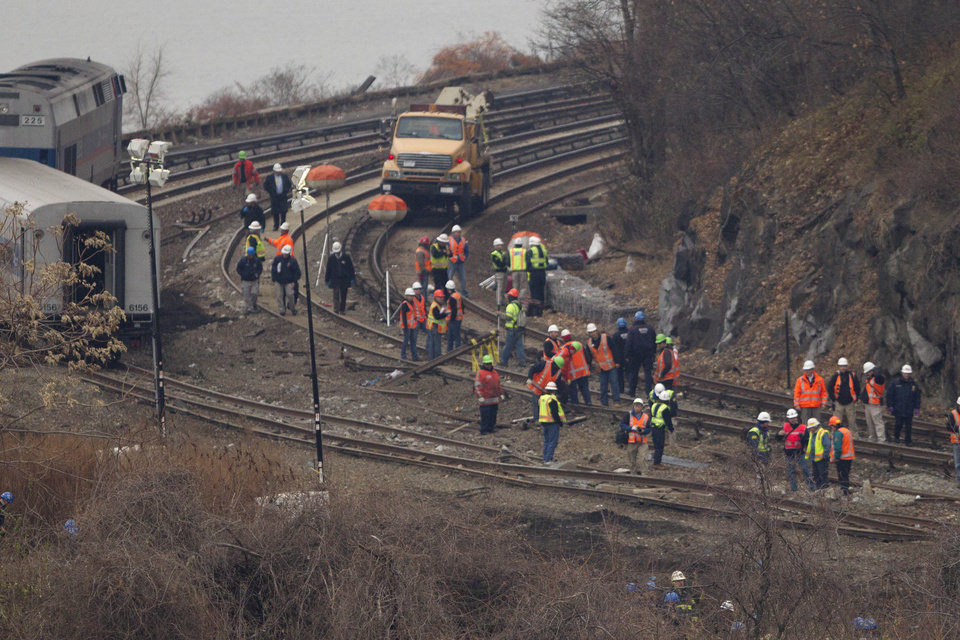 Photo - Officials look at the damaged tracks, Monday, Dec. 2, 2013 in the Bronx borough of New York where a train derailed on Sunday, killing 4 people and injuring about 60. A second data recorder was retrieved Monday from the train involved in a deadly derailment, and investigators planned interviews with the engineer and conductor in their search for the cause of the crash. On the left are a passenger car and locomotive which were part of the derailed train. (AP Photo/Mark Lennihan)