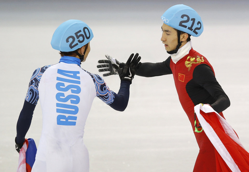 Photo - Victor An of Russia, left, celebrates his first place finish with second place finisher Wu Dajing of China following the men's 500m short track speedskating final at the Iceberg Skating Palace during the 2014 Winter Olympics, Friday, Feb. 21, 2014, in Sochi, Russia. (AP Photo/Vadim Ghirda)