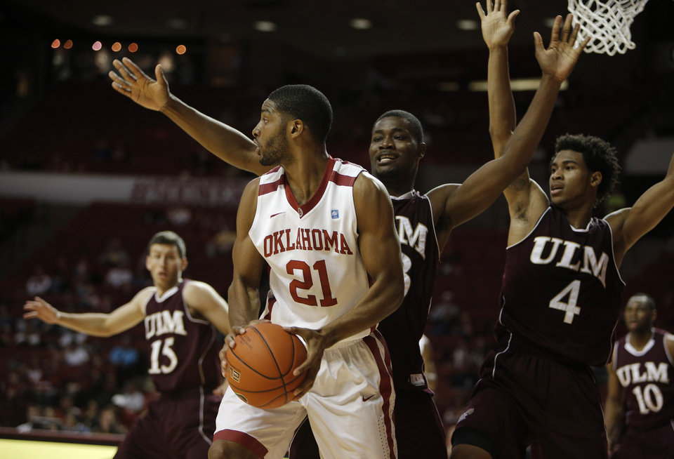 Photo - Oklahoma's Cameron Clark (21) looks for a pass away from Louisiana's Millaun Brown (23) and R.J. McCray (4) during a men's college basketball game between the University of Oklahoma and the University of Louisiana-Monroe at the Loyd Noble Center in Norman, Okla., Sunday, Nov. 11, 2012.  Photo by Garett Fisbeck, The Oklahoman