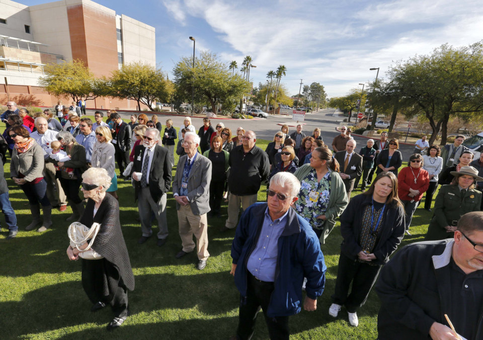 Photo - People assemble on the lawn outside University of Arizona Medical Center during a remembrance ceremony on the third anniversary of the Tucson shootings, Wednesday, Jan. 8, 2014, in Tucson, Ariz. Six people were killed and 13 wounded, including U.S. Rep. Gabrielle Giffords, D-Ariz., in the shooting rampage at a community event hosted by Giffords. The victims were all transported to the medical center in 2011.  Jared Lee Loughner was sentenced in November 2012 to seven consecutive life sentences, plus 140 years, after he pleaded guilty to 19 federal charges in the shooting. (AP Photo/Matt York)