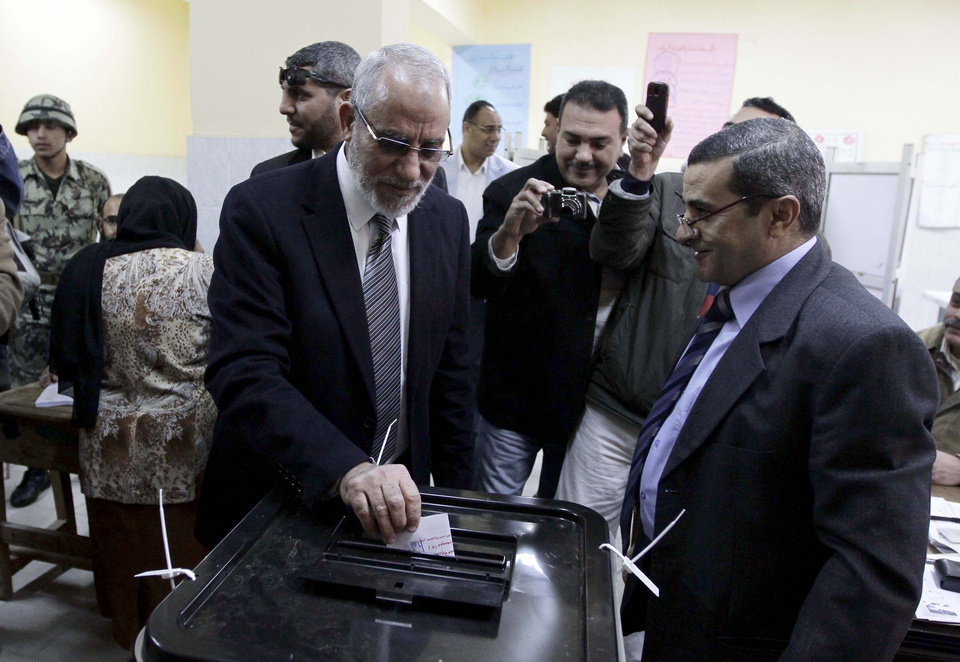 Photo - Muslim Brotherhood leader Mohammed Badie, second right, waits in line outside a polling place in Beni Suef, Egypt, to vote on a constitution drafted by Islamist supporters of President Mohammed Morsi, Saturday, Dec. 22, 2012. (AP Photo/Mohamed Nohan, El Shorouk Newspaper)EGYPT OUT