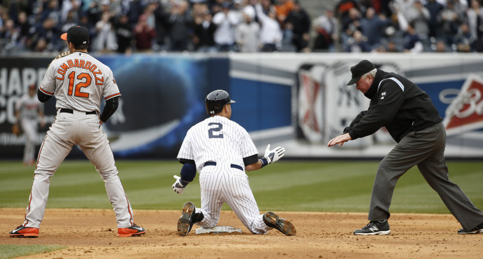 Photo - Second base umpire Tim Welke calls New York Yankees' Derek Jeter (2) safe as Jeter and Baltimore Orioles second baseman Stephen Lombardozzi (12) react after Jeter ran out a double in the fifth inning of  the Yankees home opener baseball game against the Baltimore Orioles, at Yankee Stadium in New York, Monday, April 7, 2014. (AP Photo/Kathy Willens)