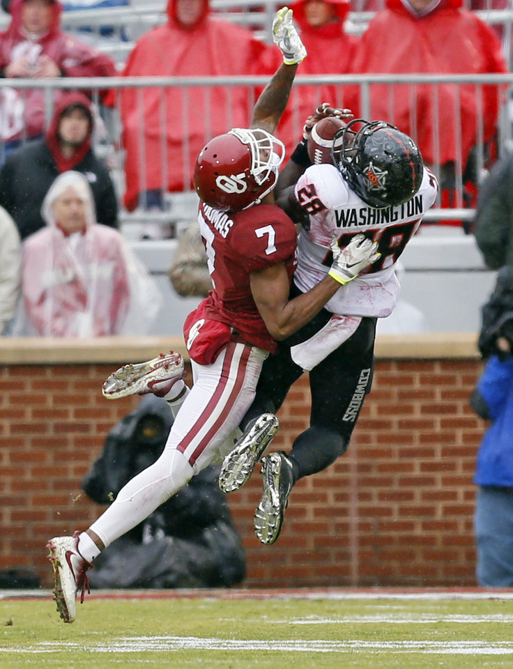 Photo - Oklahoma State's James Washington (28) makes a catch against Oklahoma's Jordan Thomas (7) in the second quarter during the Bedlam college football game between the Oklahoma Sooners (OU) and the Oklahoma State Cowboys (OSU) at Gaylord Family - Oklahoma Memorial Stadium in Norman, Okla., Saturday, Dec. 3, 2016. Photo by Nate Billings, The Oklahoman