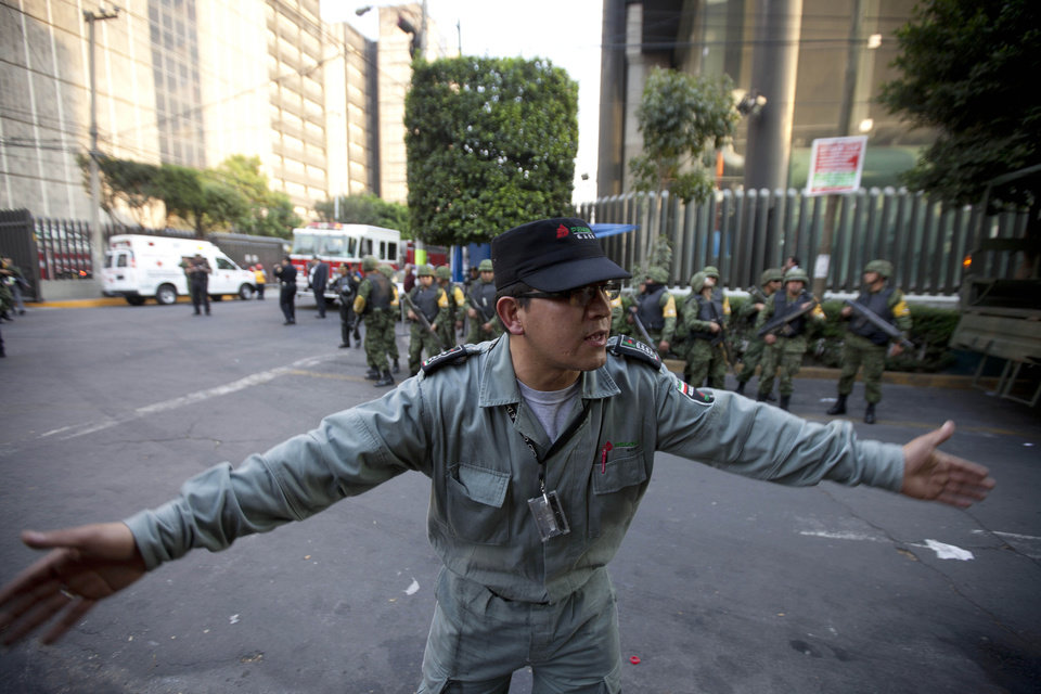Photo - A worker belonging to Mexico's state-owned oil company PEMEX keeps journalists away after an explosion at an adjacent building to the executive tower of PEMEX in Mexico City, Thursday Jan. 31, 2013. An explosion at the main headquarters of Mexico's state-owned oil company in the capital Thursday left at least several workers injured, blew out windows and damaged the building, the company said. (AP Photo/Eduardo Verdugo)