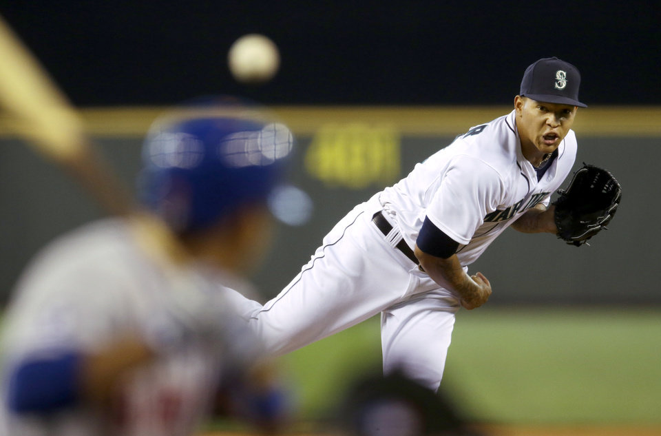 Photo - Seattle Mariners starting pitcher Taijuan Walker watches a pitch that hit New York Mets' Ruben Tejada in the helmet in the fifth inning of a baseball game, Wednesday, July 23, 2014 in Seattle. Tejada left the game and did not complete his at-bat. (AP Photo)