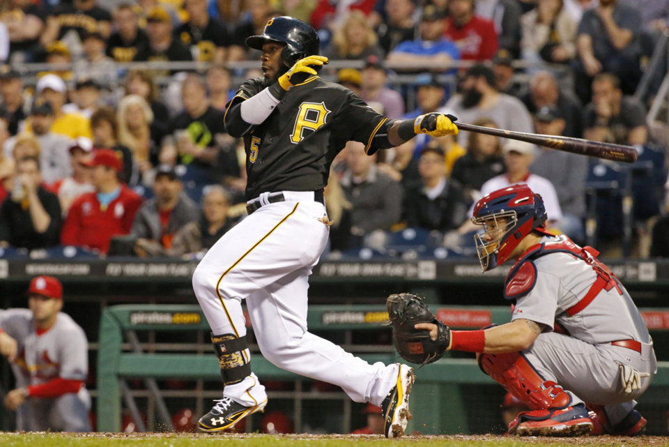 Photo - Pittsburgh Pirates' Josh Harrison (5) drives in a run with a single off St. Louis Cardinals starting pitcher Lance Lynn during the fourth inning of a baseball game in Pittsburgh, Saturday, May 10, 2014. (AP Photo/Gene J. Puskar)