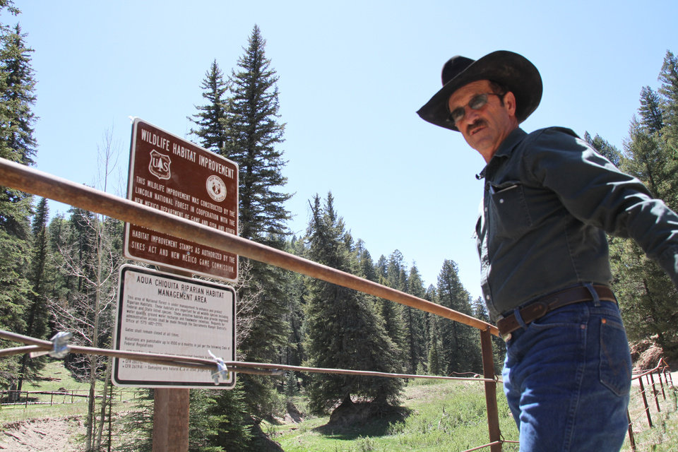 Photo - Otero cattle rancher association President Gary Stone inspects a newly posted warning sign in Weed, New Mexico, Thursday, May 15, 2014. The Otero County Cattleman's Association is pitted against the National Forest Service over a fence intended to protect wildlife that the agency installed around a small creek where the ranchers' cattle drink water. (AP Photo/Juan Carlos Llorca)