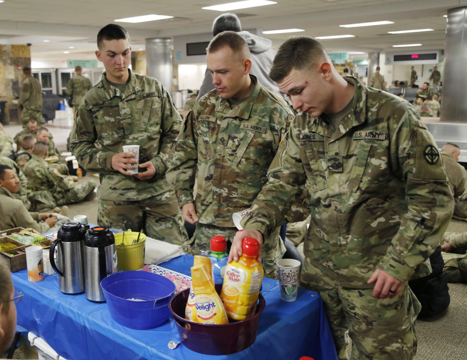 Photo - Trever Weber, from Alabama, left, Matthew Fallon, from Maryland, and Jessie Jones, from Alabama, prepare coffee provided by the YMCA, as soldiers from Ft. Sill gather at Will Rogers World Airport in Oklahoma City, Okla. on their way home for Christmas, Monday, Dec. 19, 2016.  Photo by Paul Hellstern, The Oklahoman