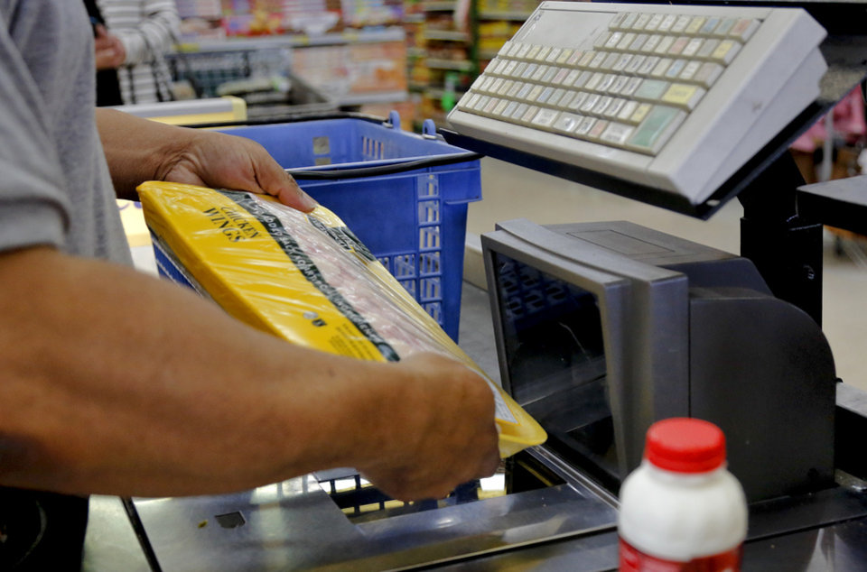 Photo - An employee works the register at the grocery store located at the corridor of N.W. 23rd St. and Martin Luther King Ave. in Oklahoma City .   Photo by Chris Landsberger, The Oklahoman  CHRIS LANDSBERGER - CHRIS LANDSBERGER