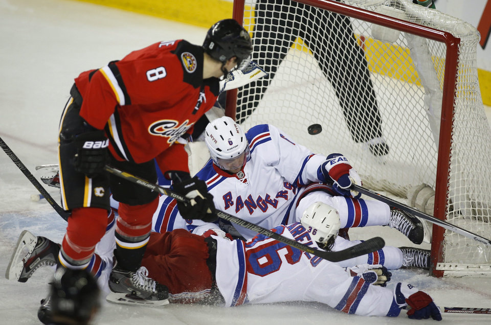 Photo - New York Rangers' Mats Zuccarello,right, from Norway, and Anton Stralman, center, from Sweden, try to block the net as Calgary Flames' Joe Colborne scores during the first period of an NHL hockey game in Calgary, Alberta, Friday, March 28, 2014. (AP Photo/The Canadian Press, Jeff McIntosh)
