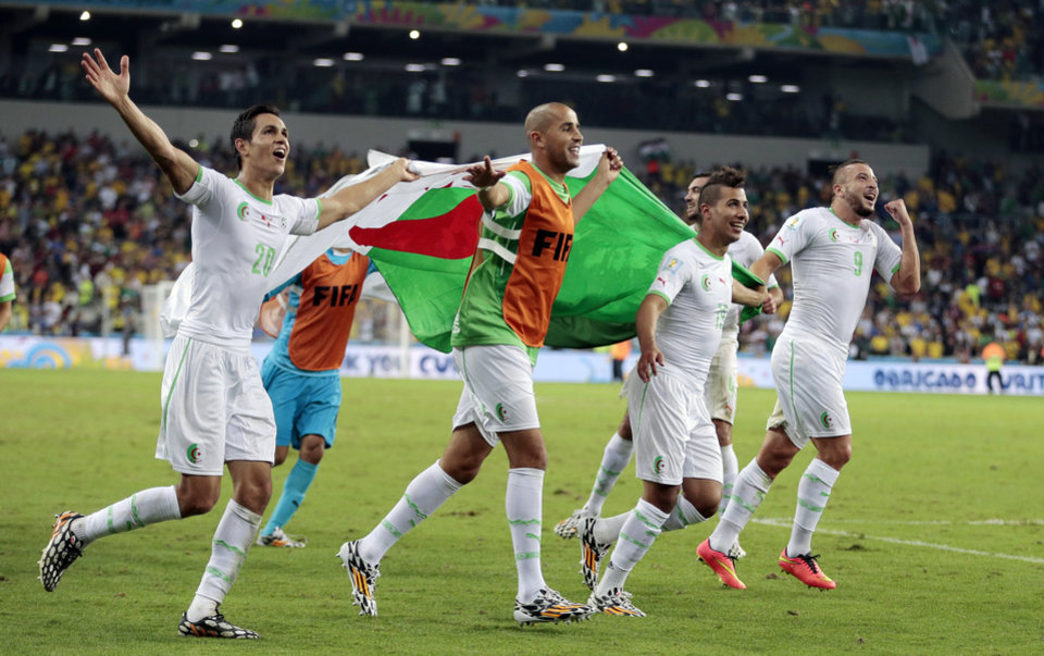 Photo - Algerian players celebrate after the group H World Cup soccer match between Algeria and Russia at the Arena da Baixada in Curitiba, Brazil, Thursday, June 26, 2014. The match ended in a 1-1 draw, but Algeria qualified for the round of 16. (AP Photo/Ivan Sekretarev)
