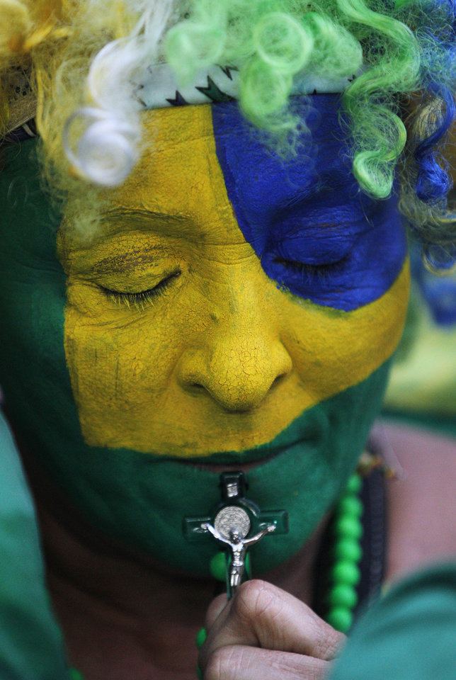 Photo - A Brazil soccer fan, with her face painted with the national colors, holds a crucifix, as she watches her team lose the World Cup semi-finals match against Germany on a live telecast inside the FIFA Fan Fest area on Copacabana beach in Rio de Janeiro, Brazil, Tuesday, July 8, 2014. (AP Photo/Leo Correa)