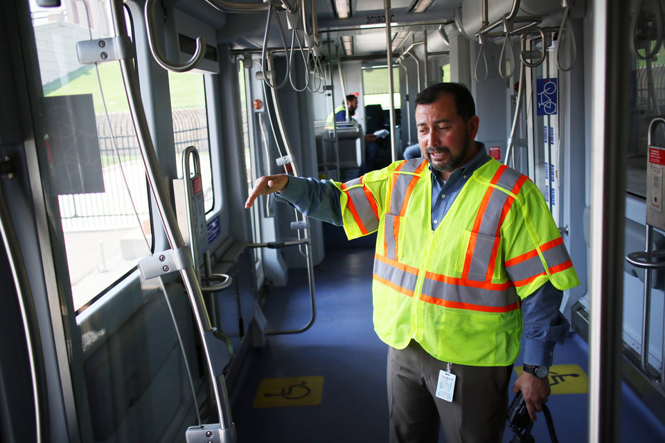 Photo -  Operations manager, Joel Garcia explains features on the streetcar. [Photo by Doug Hoke, The Oklahoman]