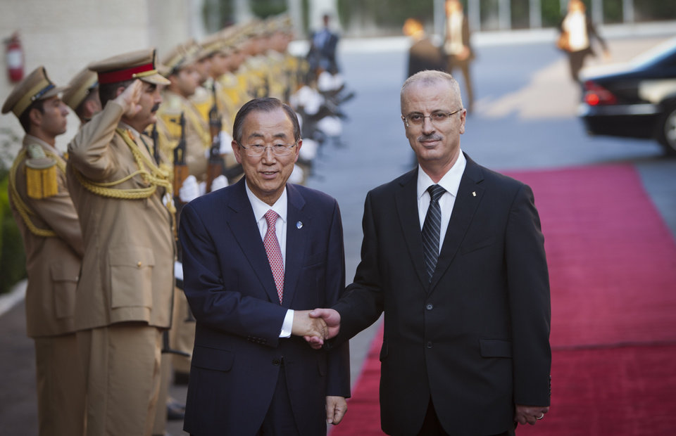 Photo - United Nations Secretary-General Ban Ki-moon, left, shakes hands with Palestinian Prime Minister Rami Hamdallah upon his arrival in the West Bank city of Ramallah, Tuesday, July 22, 2014. The two men were set to hold a joint news conference regarding the Israel-Hamas conflict. (AP Photo/Majdi Mohammed)