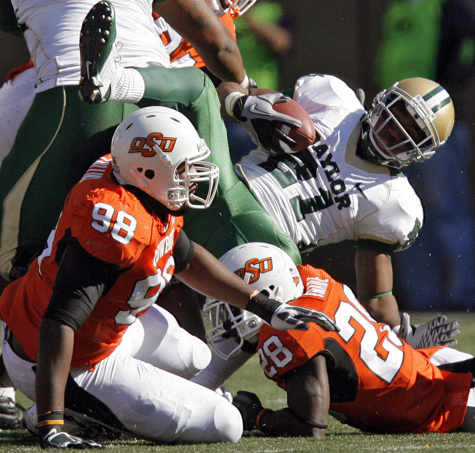 Oklahoma State's Davideli Collins (98) and Deion Imade (28) bring down Baylor's Jared Salubi (21) during the college football game between the Oklahoma State University Cowboys (OSU) and the Baylor University Bears at Boone Pickens Stadium in Stillwater, Okla., Saturday, Nov. 6, 2010. Photo by Chris Landsberger, The Oklahoman