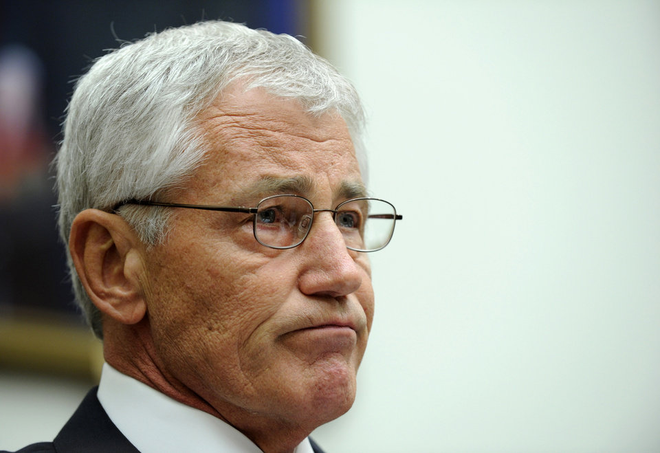 Photo - Defense Secretary Chuck Hagel listens while testifying on Capitol Hill in Washington, Wednesday, June 11, 2014, before the House Armed Services Committee. Hagel faced angry lawmakers becoming the first Obama administration official to testify publicly about the controversial prisoner swap with the Taliban. (AP Photo/Susan Walsh)