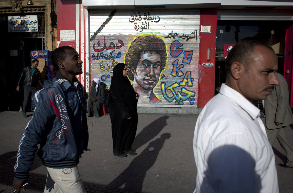 Egyptians walk past a mural depicting a man who was killed during the revolution with Arabic that reads