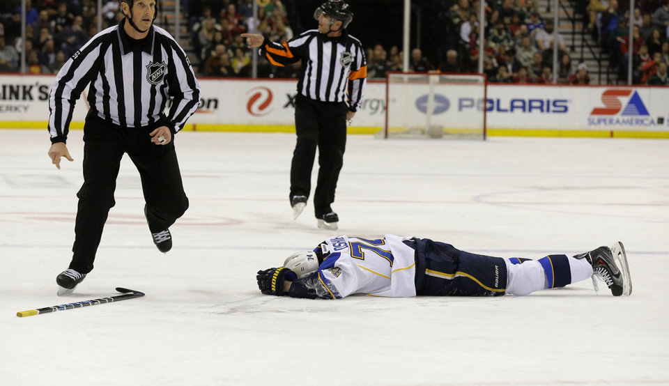 Photo - St. Louis Blues right wing T.J. Oshie (74) lies on the ice after being injured during the second period of an NHL hockey game against the Minnesota Wild in St. Paul, Minn., Thursday, April 10, 2014. Oshie left the game. The Wild won 4-2. (AP Photo/Ann Heisenfelt)