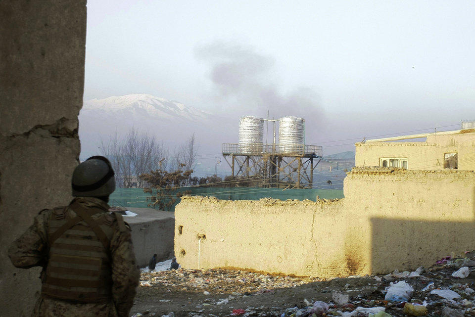 An Afghan security officer looks at smoke rising from a rocket fired by militants which landed near the Kabul traffic police headquarters during an attack in Kabul, Afghanistan, Monday, Jan. 21, 2013. Taliban insurgents wearing suicide vests attacked the Kabul traffic police headquarters before dawn Monday, police said, and eyewitnesses heard numerous explosions while a gun battle was still raging nearly four hours later. (AP Photo/Musadeq Sadeq)