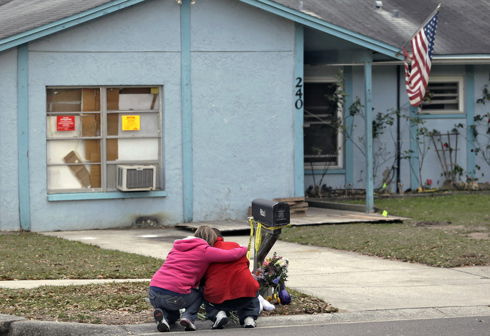 Photo - Jeremy Bush, right, is consoled by an unidentified woman Sunday, March 3, 2013, as he sits outside a home where a sinkhole opened up underneath a bedroom late Thursday evening, swallowing his brother, Jeffrey Bush, in Seffner, Fla. Crews on Sunday began the demolition of the Florida home.  (AP Photo/Chris O'Meara)