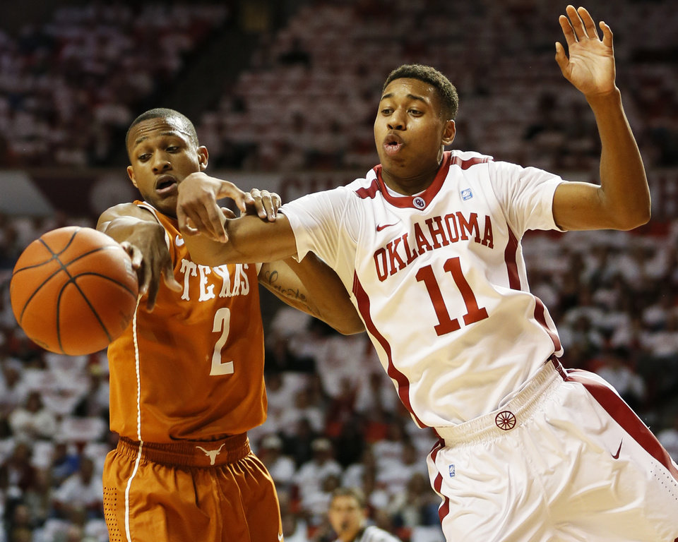 Photo - Texas' Demarcus Holland (2) knocks the ball away from Oklahoma's Isaiah Cousins (11) during a men's college basketball game between the University of Oklahoma (OU) and the University of Texas at the Lloyd Noble Center in Norman, Okla., Monday, Jan. 21, 2013. Photo by Nate Billings, The Oklahoman