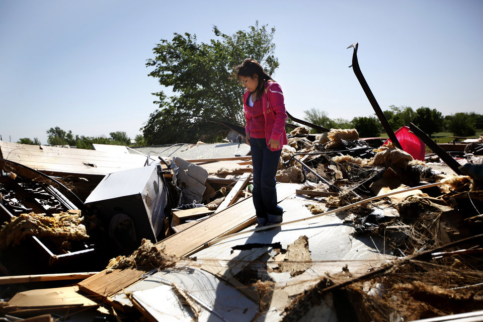 Photo - Martina Mora looks over debris from her home at Hideaway mobile home park, Sunday, April, 15, 2012. Mora was in the home with her child when the tornado struck Woodward early Sunday morning. Photo by Sarah Phipps, The Oklahoman.