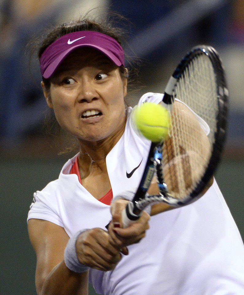 Photo - Li Na, of China, returns a shot to Flavia Pennetta, of Italy, at the BNP Paribas Open tennis tournament, Friday, March 14, 2014, in Indian Wells, Calif. (AP Photo/Mark J. Terrill)