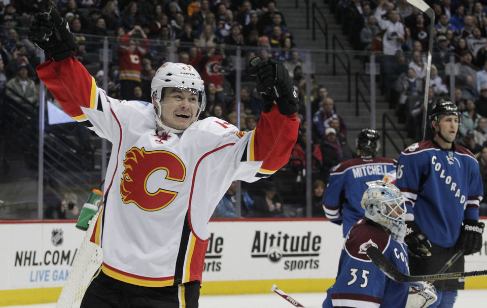 Photo - Calgary Flames left wing Jiri Hudler (24) celebrates his goal in the second period of an NHL game against the Colorado Avalanche in Denver on Monday, Jan. 6, 2014. Colorado Avalanche goalie Jean-Sebastien Giguere (35) and Avalanche defenseman Cory Sarich (16) stand in the crease. (AP Photo/Joe Mahoney)