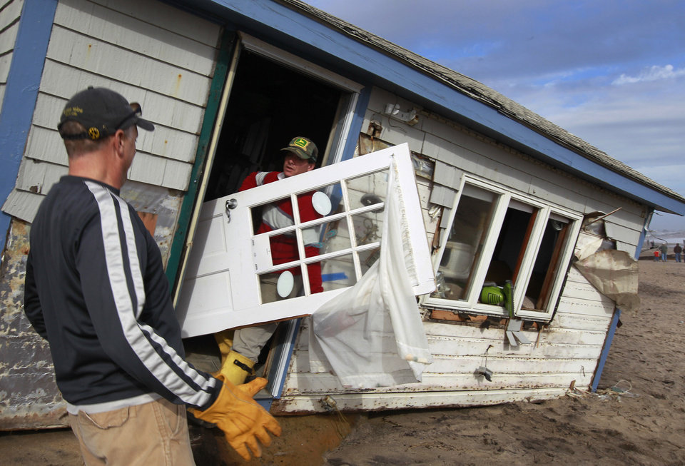 Christopher Hannafin, center, and Pete Duhamel, left, both of South Kingstown, R.I., salvage items, including a door, from a friend's cottage destroyed by Superstorm Sandy, on Roy Carpenter's Beach, in the village of Matunuck, in South Kingstown, Tuesday, Oct. 30, 2012. Sandy, the storm that made landfall Monday, caused multiple fatalities, halted mass transit and cut power to more than 6 million homes and businesses. (AP Photo/Steven Senne) ORG XMIT: RISR107