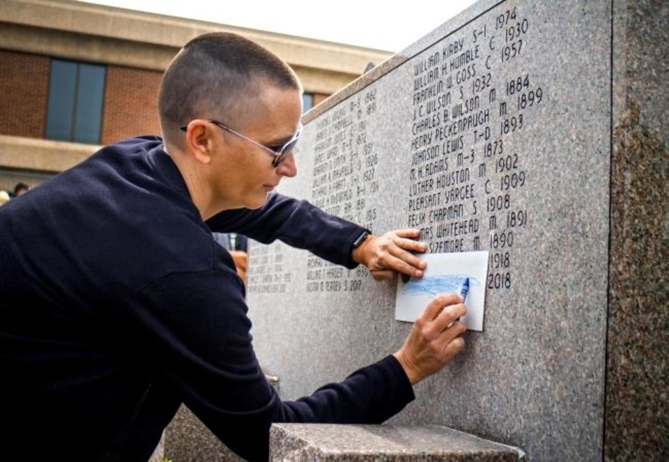 Photo -  Cara Martin traces the name of her late husband Oklahoma Highway Patrol Trooper Daniel B. Martin off the memorial wall during the 51st Annual Oklahoma Law Enforcement Officer's Memorial Service at The Oklahoma Law Enforcement Memorial in Oklahoma City on Friday. Trooper Martin passed away in May 2018. [Chris Landsberger/The Oklahoman]